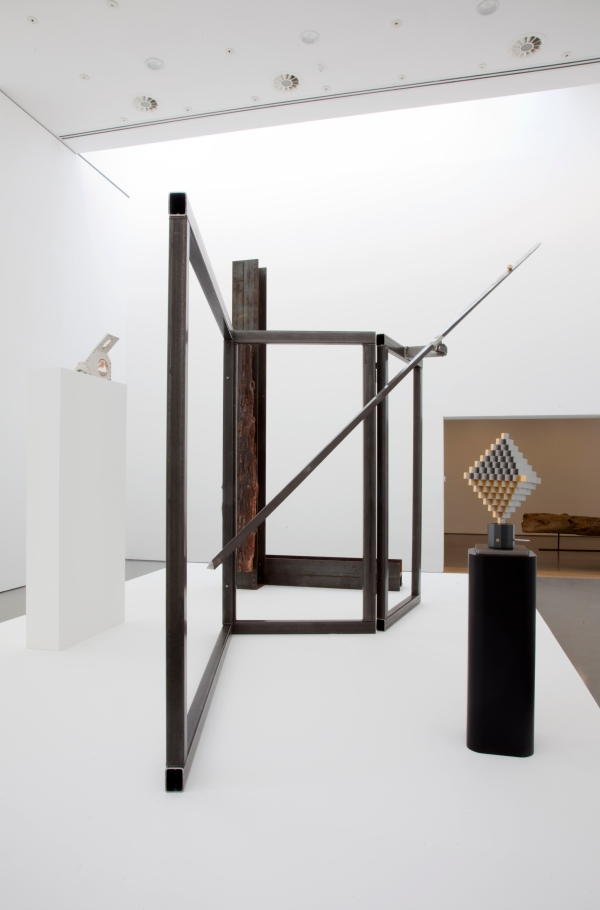 A closer view of 'For Asta' (the steel frame) and 'Cretaceous' (the vertical wood bound to a girder (both 2014) by Carol Bove, with a pedestal supporting 'Crescita' (1968) by Carlo Scarpa.