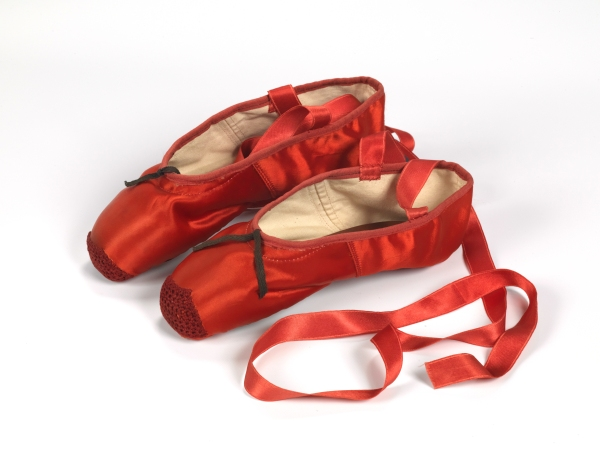 Red ballet shoes made for Victoria Page (Moira Shearer) in The Red Shoes (1948), silk satin, braid and leather, England Artist: Freed of London (founded in 1929), Date: 1948 . Photograph reproduced with the kind permission of Northampton Museums and Art Gallery.