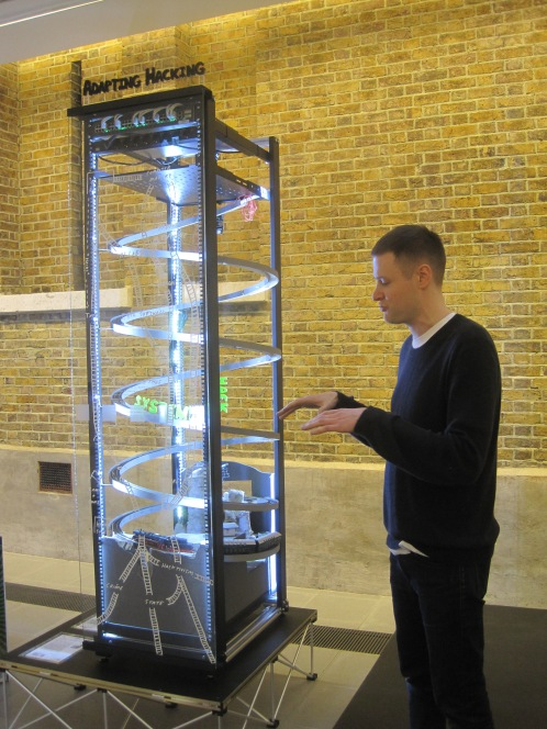Simon Denny introduces Modded Server Rack Display: Adapting Hacking (2015) at the Serpentine Sackler Gallery. Photo: Simon Port