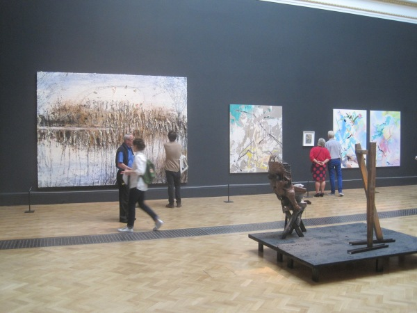 View of the Lecture Room including, from left to right, Und Du Bist Maler Geworden by Anselm Kiefer, Painting For B by Secundino Hernández, and She Pricked Her Finger Cutting the Clouds and Many-Coloured Messenger Seeks Her Fortune by Fiona Rae RA
