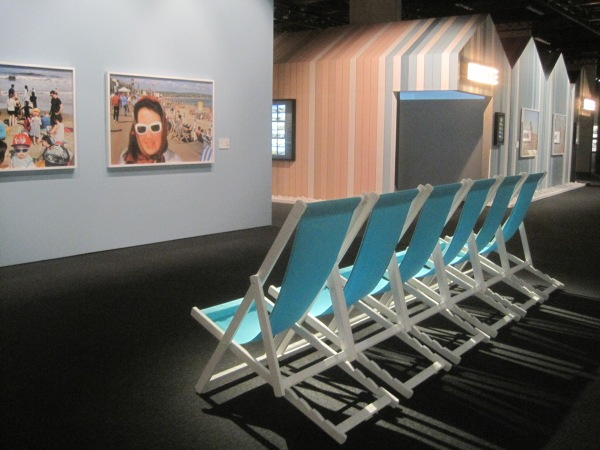 Installation view of The Great British Seaside showing deckchairs facing two photos by Martin Parr with the Seaside Cinema in the background