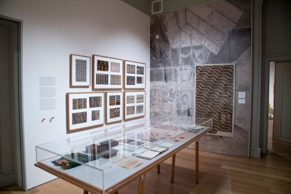 Installation view of Enid Marx at the House of Illustration showing the wall-sized sketch of Marx's flat by Eric Ravilious, wall cases of fabrics and a central display of tools. Photo by Paul Grover
