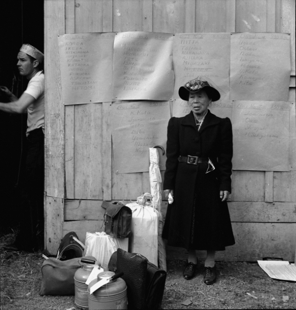 Centerville, California by Dorothea Lange. This evacuee stands by her baggage as she waits for evacuation bus. Evacuees of Japanese ancestry were housed in War Relocation Authority centers for the duration, 1942. Courtesy National Archives