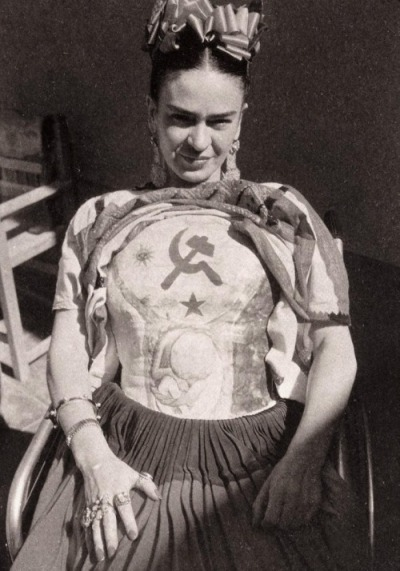 Frida Kahlo wearing a plaster cast, which she decorated with the hammer and sickle (c.1950) photo by Florence Arquin