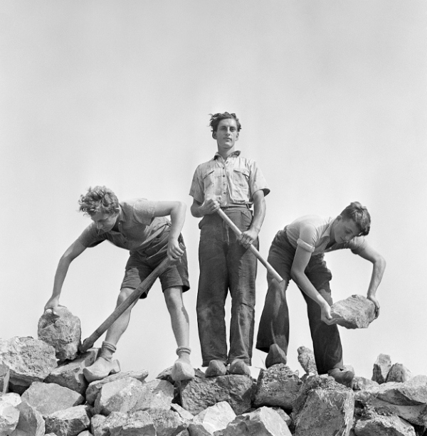 Ernst Kaufmann, center, and unidentified Zionist youth, wearing clogs while learning construction techniques in a quarry, Werkdorp Nieuwesluis, Wieringermeer, The Netherlands (1938–39) by Roman Vishniac © Mara Vishniac Kohn