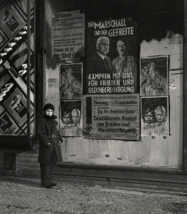Vishniac's daughter Mara posing in front of an election poster for Hindenburg and Hitler that reads 'The Marshal and the Corporal: Fight with Us for Peace and Equal Rights', Wilmersdorf, Berlin (1933) © Mara Vishniac Kohn