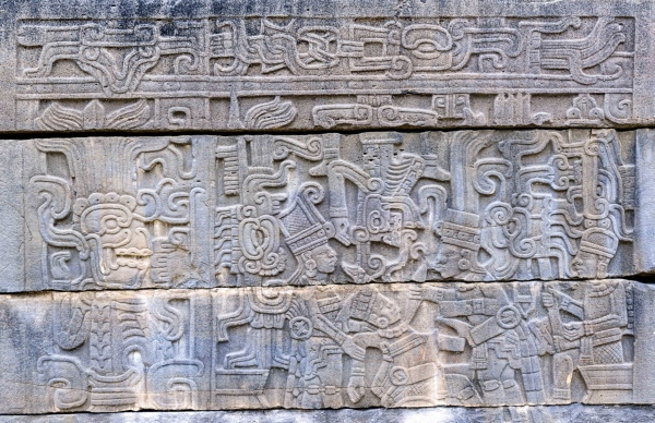 Carved panel, South Ballcourt, El Tajin. A loser at the ballgame is being sacrificed by two victors while a third man looks on. A death god descends from the skyband above to accept the offering. Late Classic.