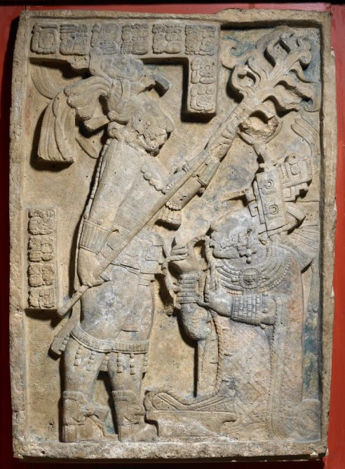 A carved lintel from a building at Yaxchilan depicts a bloodletting ritual. The king of Yaxchilan, Shield Jaguar II, is holding a flaming torch over his wife, Lady K'ab'al Xook, who is pulling a thorny rope through her tongue. Scrolls of blood can be seen around her mouth.