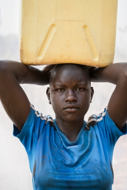 Sarah, aged 13, carries a five gallon jerrycan of water home three times a day from the series the Women of Rutal Uganda by Dan Nelken © Dan Nelken