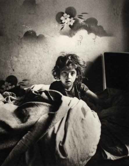 Sara, sitting in bed in a basement dwelling, with stencilled flowers above her head, Warsaw (c.1935-37) © Mara Vishniac Kohn