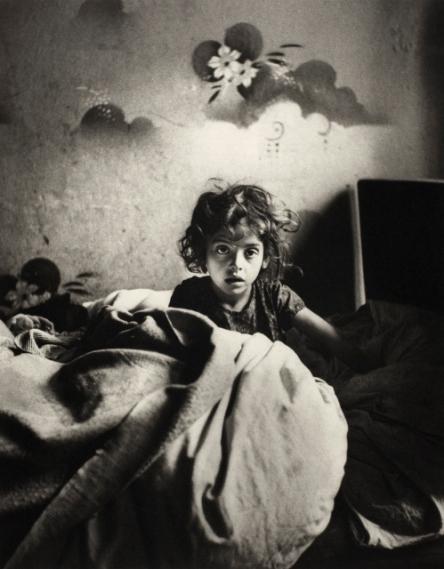 Sara, sitting in bed in a basement dwelling, with stencilled flowers above her head, Warsaw (c.1935-37) © Mara Vishniac Kohn