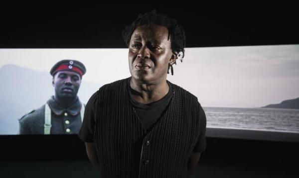 John Akomfrah in front of Mimesis: African Soldier, co-commissioned by 14-18 NOW, New Art Exchange, Nottingham and Smoking Dogs Films, with additional support from Sharjah Art Foundation. Photo © IWM / Film © Smoking Dogs Films